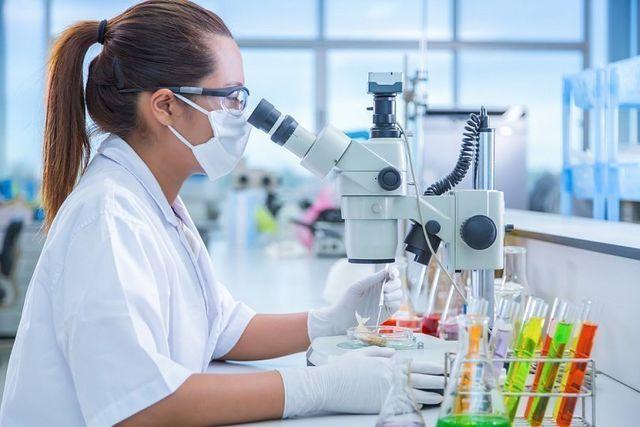 Женщина смотри в микроскоп
