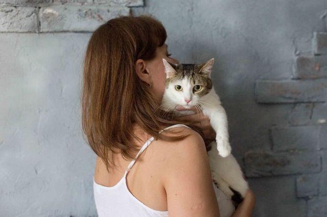 Женщина обнимает кошку